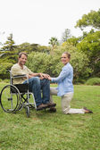 Attractive man in wheelchair with partner kneeling beside him — Stock Photo