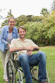 Szczęśliwy człowiek na wózku inwalidzkim z partnerem — Zdjęcie stockowe