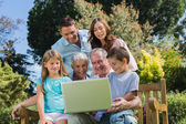 Smiling multi generation family with a laptop sitting in park — Stock Photo