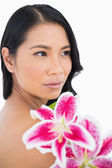 Pensive natural brown haired model posing with lily — Stock Photo