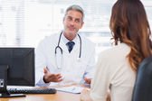 Smiling doctor talking with his patient — Stock Photo