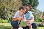 Cheerful dad and son inspecting leaf with a magnifying glass — Stock Photo