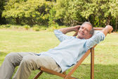 Happy mature man sitting on sun lounger — Stock Photo