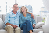 Happy couple relaxing on their couch — Stock Photo