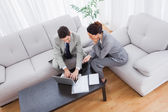Colleagues working together sitting on sofa and using laptop — Stock Photo