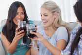 Happy friends toasting with red wine together — Stock Photo