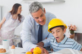 Father showing son his blueprints as he is wearing hardhat — Stock Photo