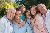 Smiling family and grandparents in the countryside embracing — Stock Photo