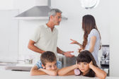 Unhappy siblings sitting in kitchen with their parents who are f — Stock Photo