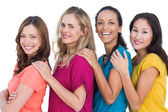 Cheerful models in a line posing with colorful t shirts — Stock Photo