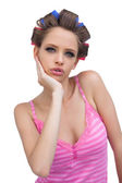 Cute young model posing wearing hair curlers — Stock Photo