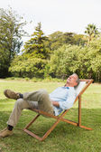 Happy man resting in sun lounger — Stock Photo
