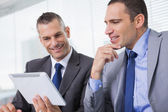 Smiling businessmen working together on their tablet — Stock Photo