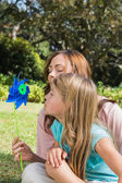 Mother with daughter blowing pinwheel in the park — Stock Photo