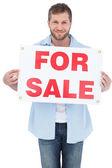 Charmante jonge man met een voor verkoop teken — Stockfoto