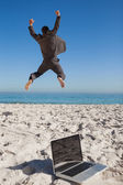 Victorious businessman in suit jumping leaving his laptop — Stock Photo