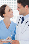 Smiling doctor and surgeon attractively looking at each other — Stock Photo