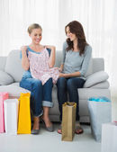 Cheerful friends looking at purchases — Stock Photo