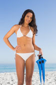 Beautiful brown haired woman in white bikini holding fins — Stock Photo