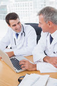 Doctors working together on laptop — Stock Photo