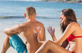 Cheerful attractive woman applying sun cream on her boyfriends b — Stock Photo