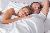 Attractive couple sleeping and cuddling in bed — Stock Photo