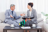 Funny businessman wearing stripey socks and talking with his col — Stock Photo