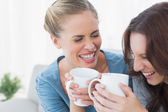 Friends bursting out laughing while having coffee — Stock Photo