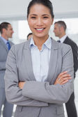 Businesswoman posing while colleagues talking together — Stock Photo