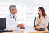 Patient talking with her doctor about illness — Stock Photo