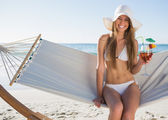 Pretty blonde wearing bikini and sunhat sitting on hammock with — Stock Photo
