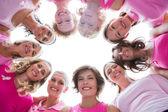 Grupp glada kvinnor i cirkel bär rosa för bröstcancer — Stockfoto