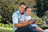 Happy dad and son with a tablet pc — Stock Photo