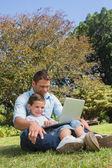 Cheerful dad and son with a laptop — Stock Photo