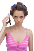 Serious woman wearing hair rollers with phone — Stock Photo