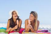 Cheerful pretty women lying on their towel eating ice cream — Stock Photo