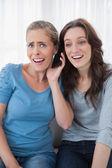 Zaskoczony przyjaciół słuchając coś intrygującego na telefon — Zdjęcie stockowe