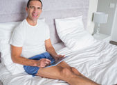 Smiling man using his tablet pc sitting on bed — Stock Photo