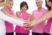 Cheerful women posing in circle holding hands wearing pink for b — Stock Photo