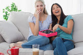 Friends laughing and sharing box of chocolates — Stock Photo