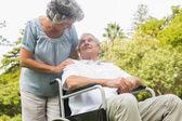 Веселый зрелый человек в инвалидной коляске, разговаривая с партнером — Стоковое фото