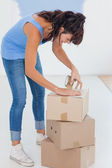 Brunette taping up moving boxes — Stock Photo