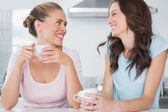 Laughing friends having cup of coffee — Stock Photo