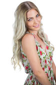 Smiling attractive blonde wearing flowered dress posing — Stock Photo