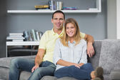 Attractive young couple sitting on their couch — Stock Photo