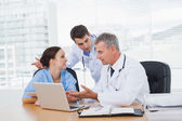 Doctors and surgeon discussing together — Stock Photo