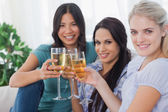 Cheerful friends enjoying white wine together smiling at camera — Stock Photo