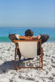 Relaxed young businessman resting on his sun lounger — Stock Photo