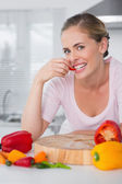 Attractive woman posing while eating vegetables — Stock Photo