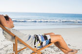 Handsome man lying on his deck chair admiring sea — Stock Photo